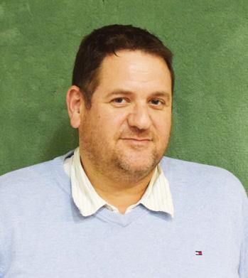 תמונת פרונט של תומר קנצוקר עם חולצה לבנה על רקע ירוק