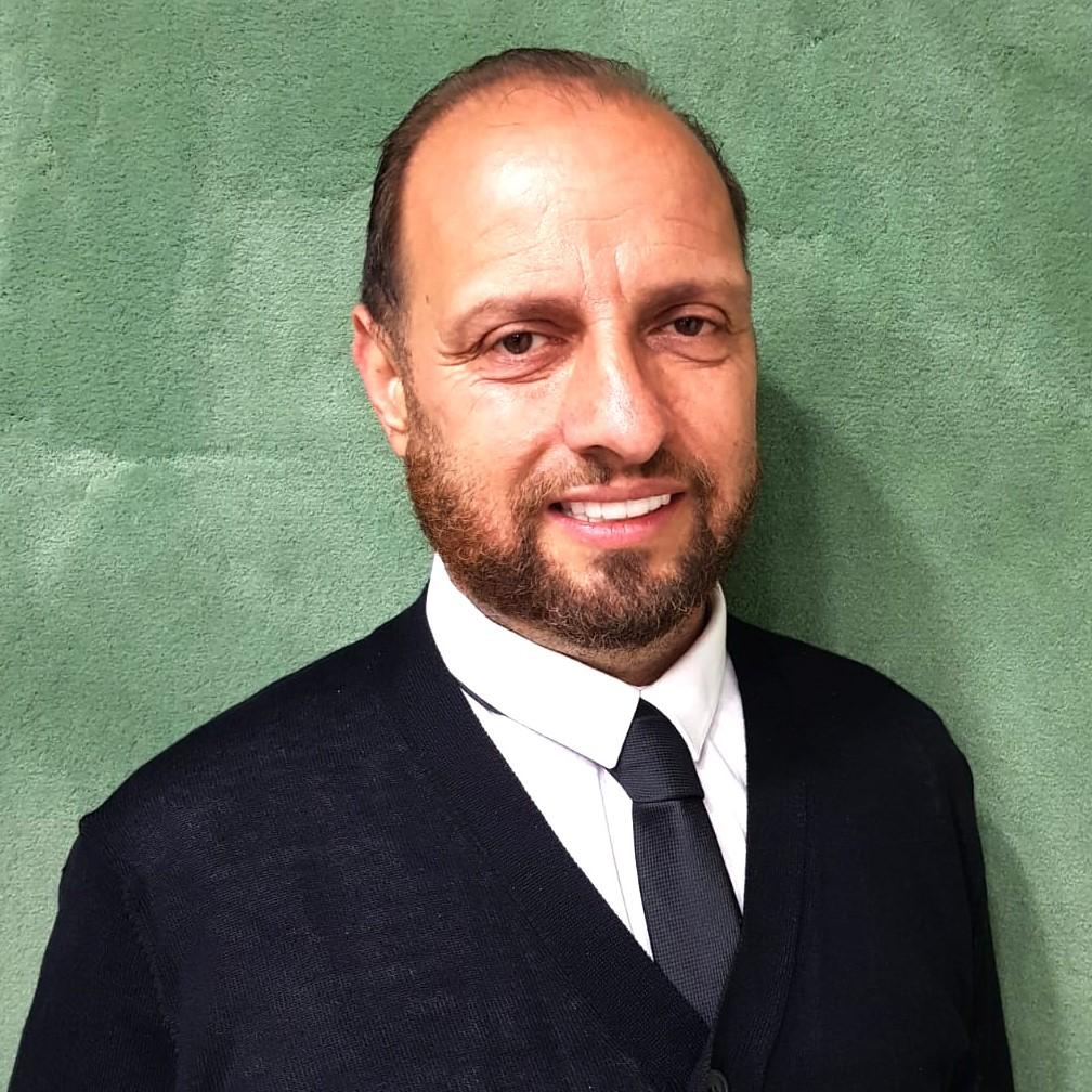תמונת פרונט של מיקי קופל עם עניבה שחורה וחולצה לבנה עם סוודר שחור על רקע ירוק