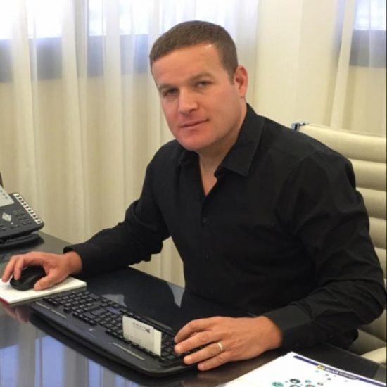 ליאור הורנצ'יק בחולצה שחורה יושב בכיסא לבן ליד שולחן משרד חום אשר עליו מונחים: מקלדת שחורה עם כרטיס לבן, עכבר מחשב שחור עם פד לבן וטלפון משרד